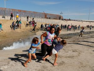 A migrant family, part of a caravan of thousands traveling from Central America en route to the United States, run away from tear gas in front of the border wall between the U.S and Mexico in Tijuana
