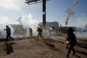 Migrants, part of a caravan of thousands traveling from Central America en route to the United States, and journalists flee tear gas released by U.S. border patrol near the fence between Mexico and the United States in Tijuana